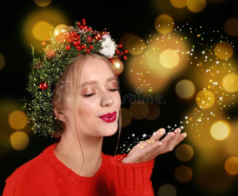 Beautiful young woman with Christmas wreath blowing magical snowy dust on color background. Bokeh effect stock photo