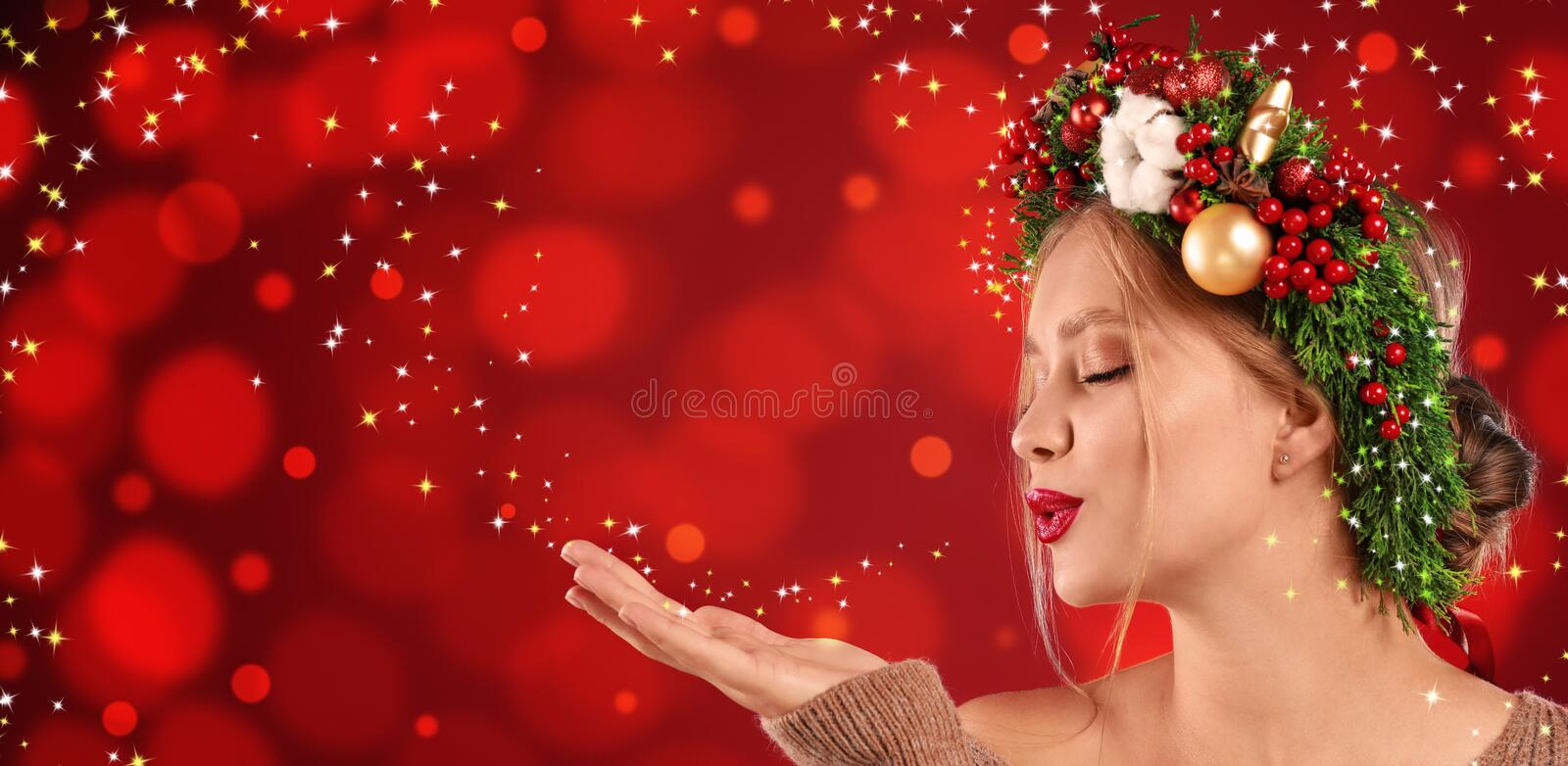 Beautiful young woman with Christmas wreath blowing magical snowy dust on red background. Bokeh effect royalty free stock photos