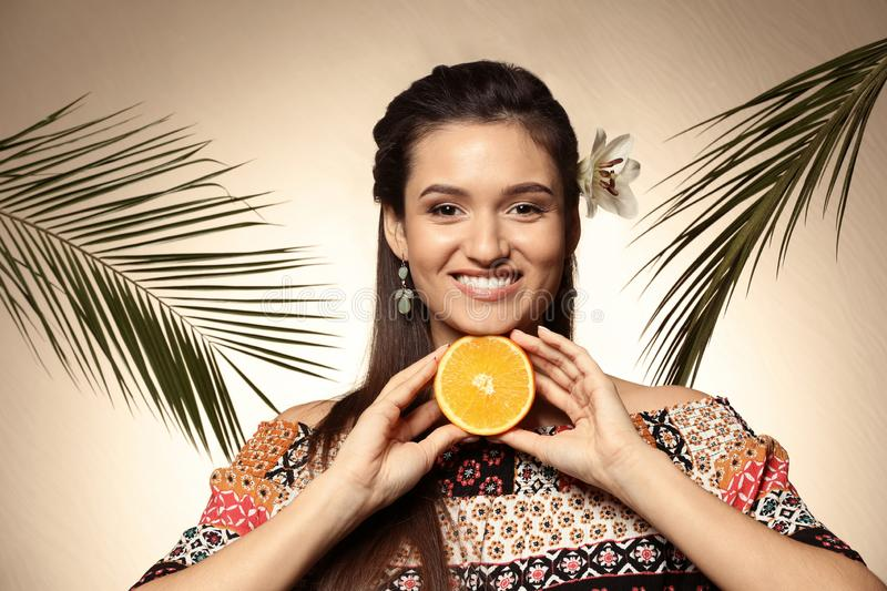 Beautiful young woman with citrus fruit and palm leaves on color background stock photo