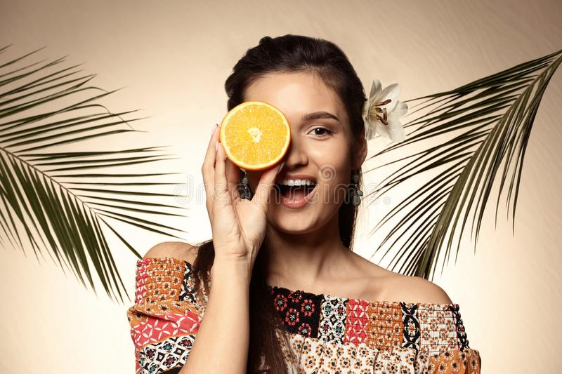 Beautiful young woman with citrus fruit and palm leaves on color background stock photos