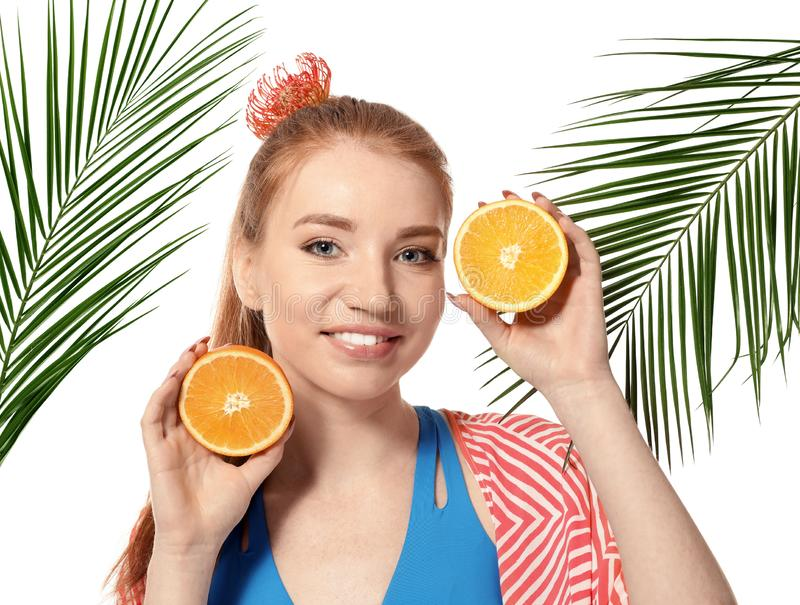 Beautiful young woman with citrus fruit and palm leaves on white background stock image