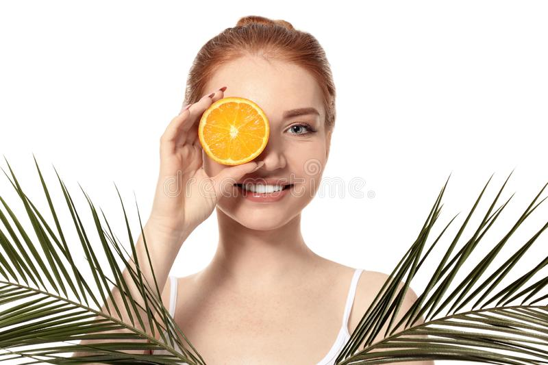 Beautiful young woman with citrus fruit and palm leaves on white background royalty free stock images