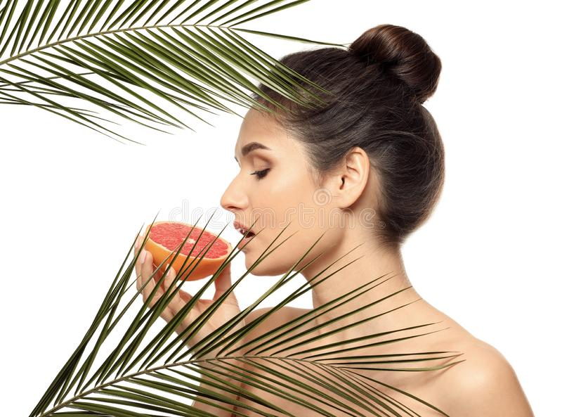 Beautiful young woman with citrus fruit and palm leaves on white background royalty free stock photography