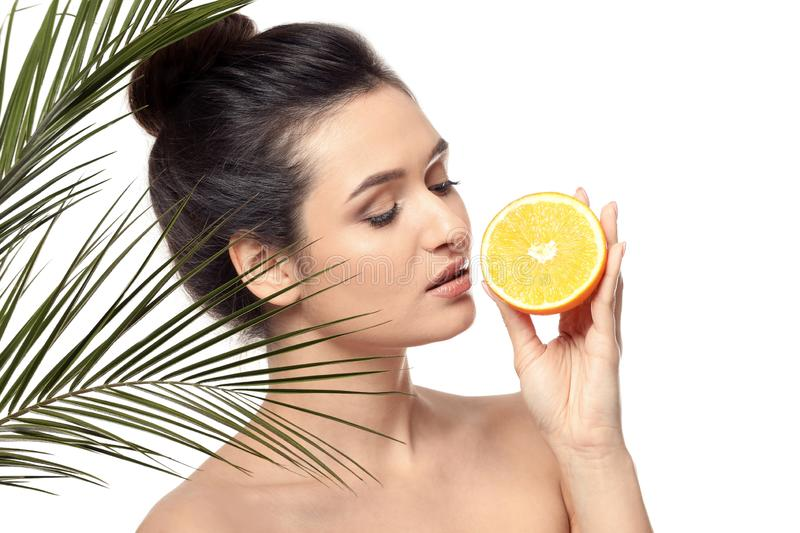 Beautiful young woman with citrus fruit and palm leaves on white background stock photography