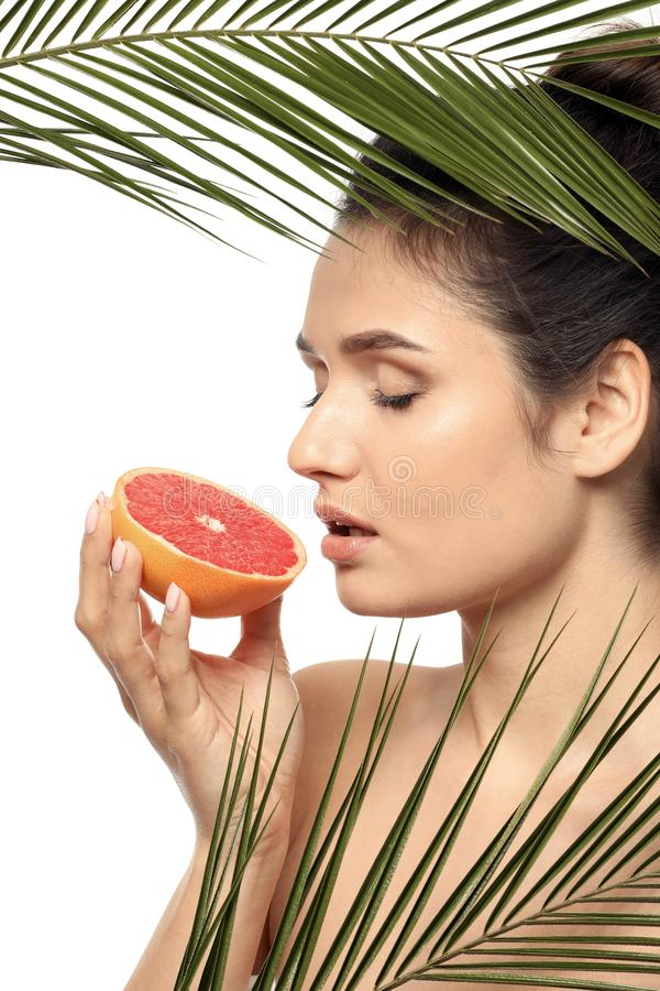 Beautiful young woman with citrus fruit and palm leaves on white background stock photo