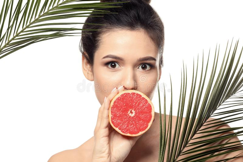 Beautiful young woman with citrus fruit and palm leaves on white background royalty free stock photos