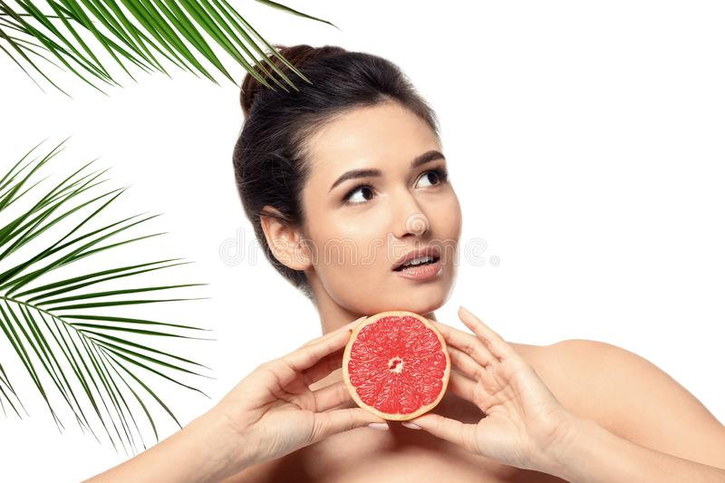 Beautiful young woman with citrus fruit and palm leaves on white background royalty free stock image