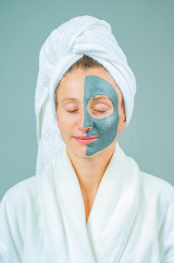 Beautiful young woman with clay facial mask. Skincare and beauty Concept stock images