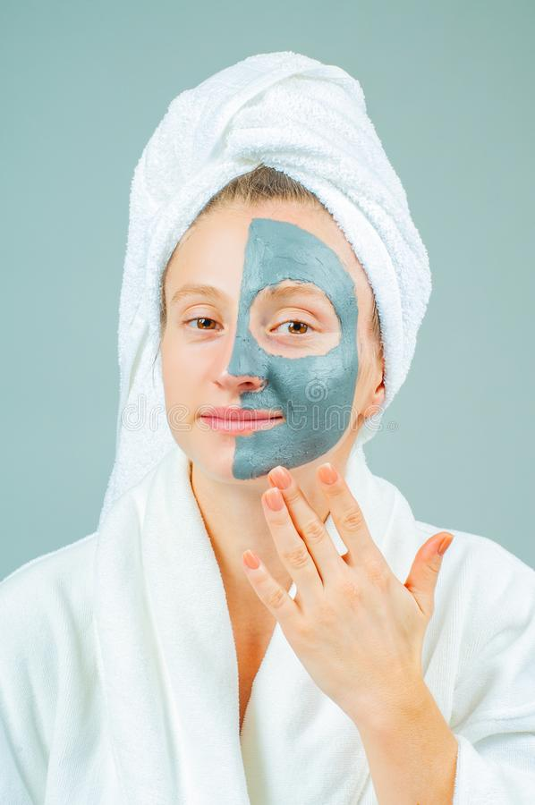 Beautiful young woman with clay facial mask. Skincare and beauty Concept stock photography