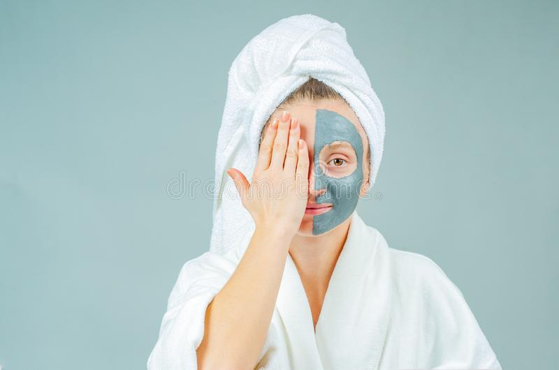 Beautiful young woman with clay facial mask. Skincare and beauty Concept stock image