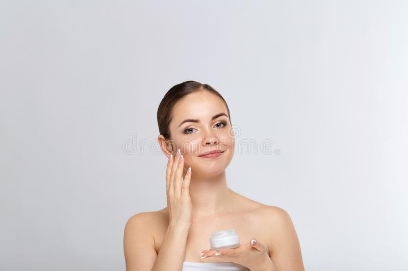 Beautiful Young Woman with Clean Fresh Skin  touch own face. Facial  treatment.  Skin care. Cosmetology, royalty free stock image