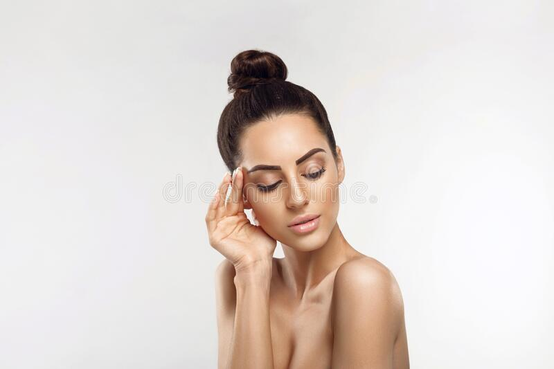Beautiful young woman with clean fresh skin touch own face. Girl holding and apply moisturizing cream. Facial  treatment. Skin car. E. Cosmetology, beauty and stock photos