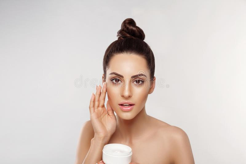 Beautiful Woman with healthy smooth facial clean skin holding bottle cosmetic cream. Model with Beauty face. Face Skin care Moistu royalty free stock images