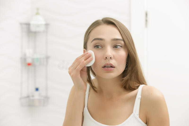 Beautiful young woman cleaning her skin with a cotton pad. Focused beautiful young woman cleaning her skin with a cotton pad, looking at the mirror at home stock photos