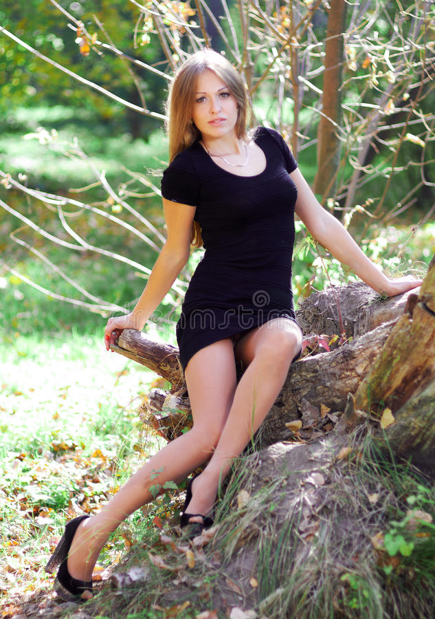 Beautiful young woman in cocktail dress and high-heeled shoes si stock image