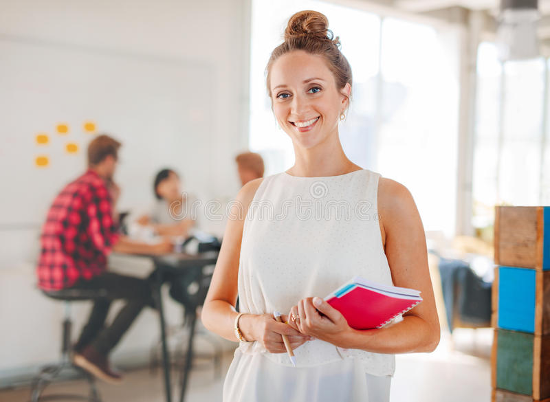Beautiful young woman with colleagues meeting in background royalty free stock photos