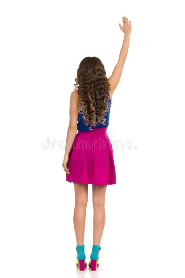 Young Woman In Colorful High Heels, Pink Mini Skirt And Blue Top Is Standing With Arm Raised And Waving. Rear View royalty free stock photo