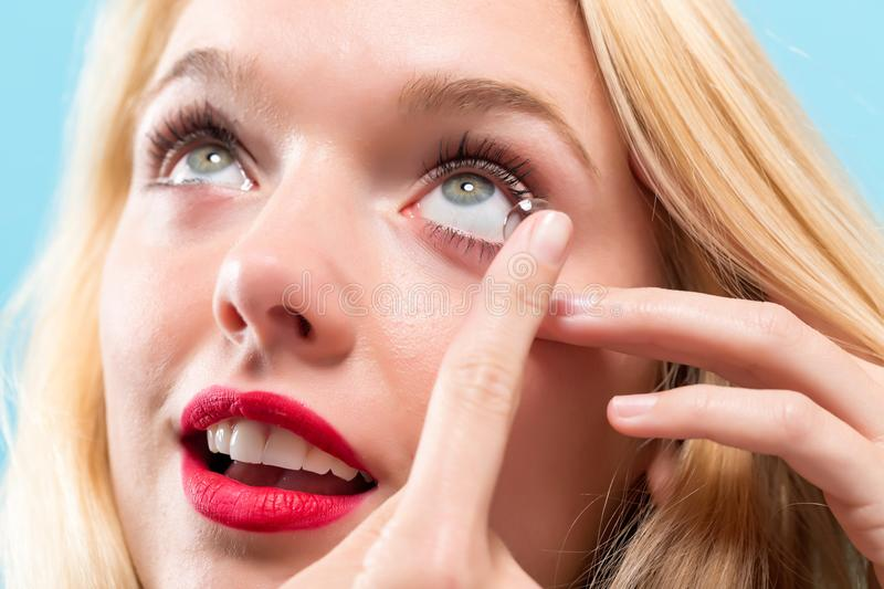 Beautiful young woman with contact lens stock images