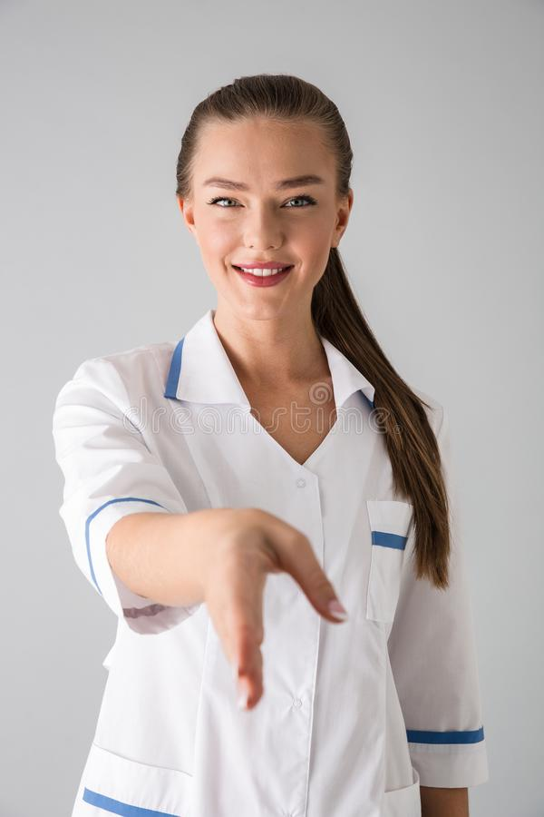 Beautiful young woman cosmetologist doctor isolated over grey wall background give you a hand for handshake stock images