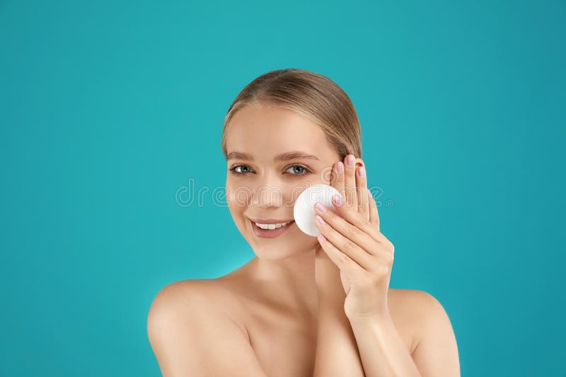 Beautiful young woman with cotton pad on background stock images