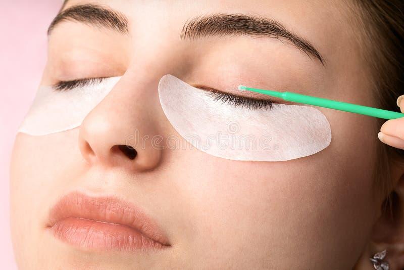 Beautiful young woman during eyelash extension stock image