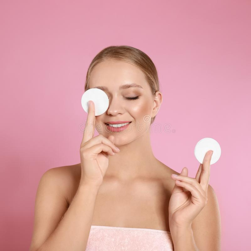Beautiful young woman with cotton pads on background stock photos