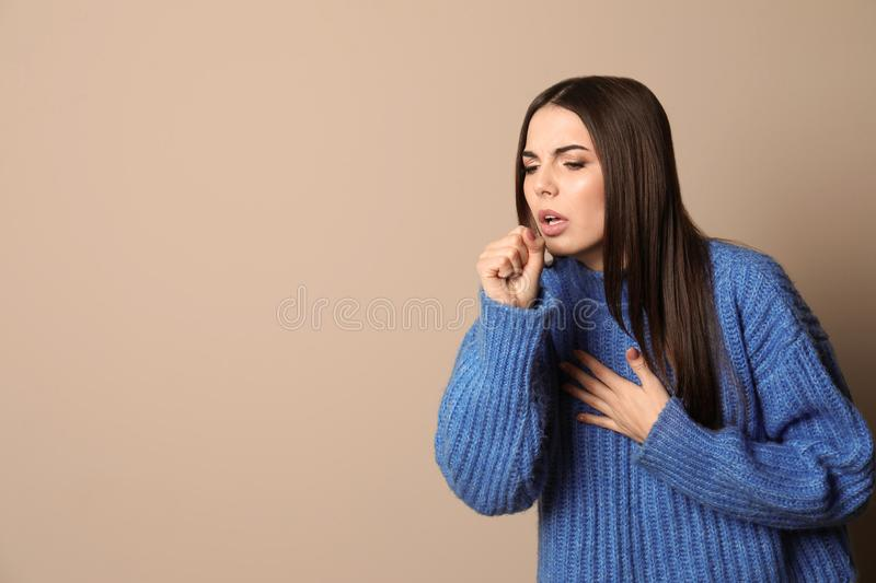 Beautiful young woman coughing against color background. Space for text royalty free stock images