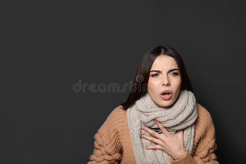 Beautiful young woman coughing against dark background. Space for text royalty free stock photography