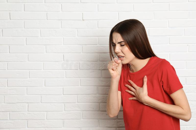 Beautiful young woman coughing near brick wall. Space for text stock image