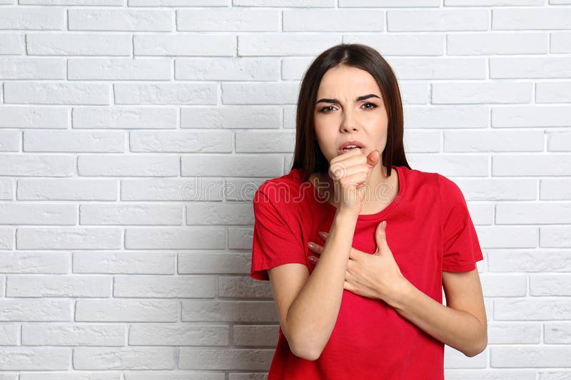 Beautiful young woman coughing near brick wall. Space for text royalty free stock photography