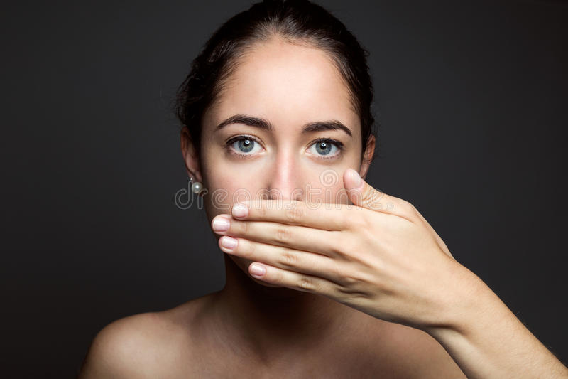 Beautiful young woman covering her mouth with hand. Isolated. stock images
