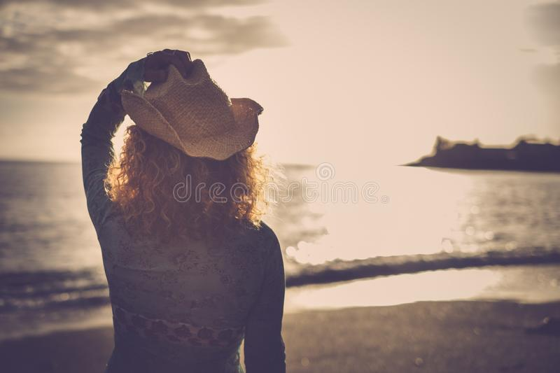 Beautiful young woman with cowboy hat and golden hair look an amazing coloured sunset over the ocean in vacation leisure anjoyed. Time. freedom and happy with stock photography