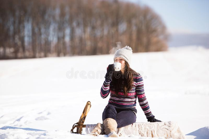Beautiful young woman with cup of coffee in winter nature stock photo