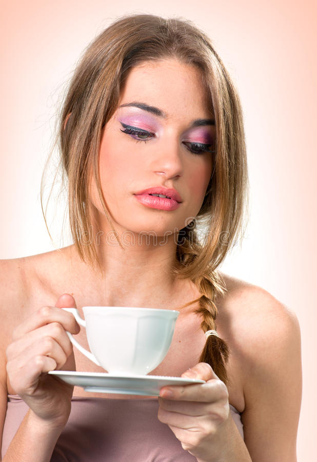Beautiful young woman with a cup of tea/coffee royalty free stock photos