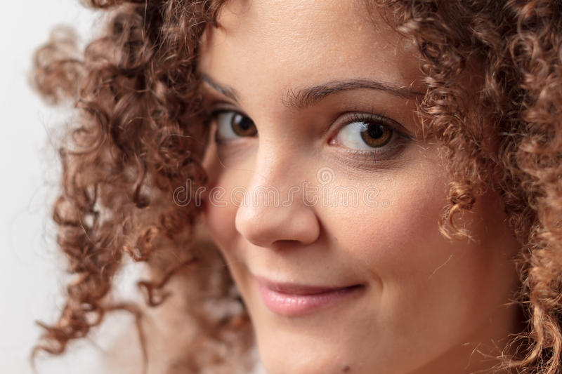 Beautiful young woman with curly hair royalty free stock photography