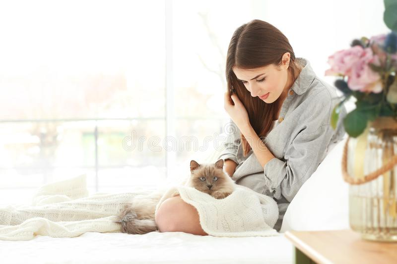Beautiful young woman with cute cat resting at home stock photos