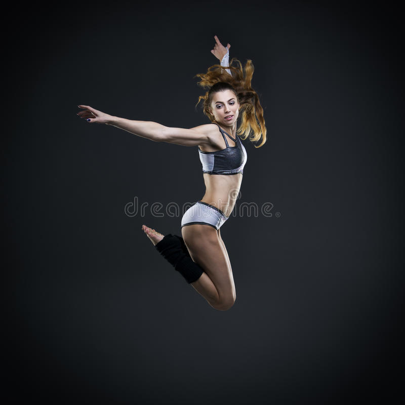 Beautiful young woman dancer jumping in studio royalty free stock photo