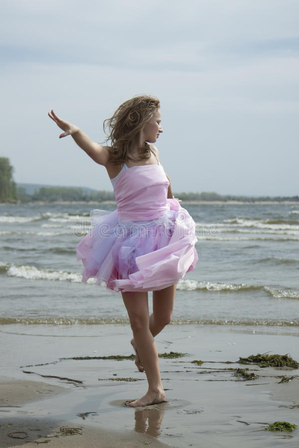 The beautiful young woman dances on a beach stock photos