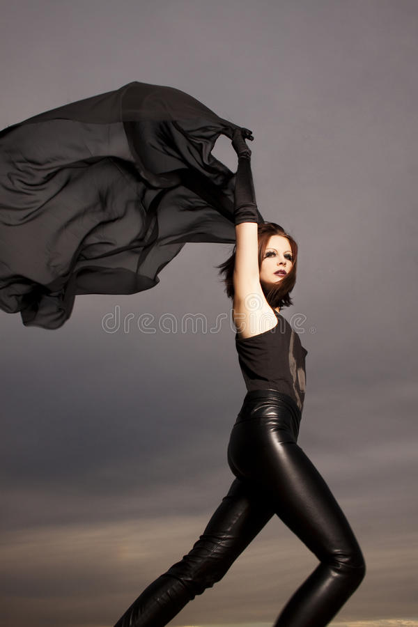 Beautiful young woman dancing. In front of a cloudy sky stock photo