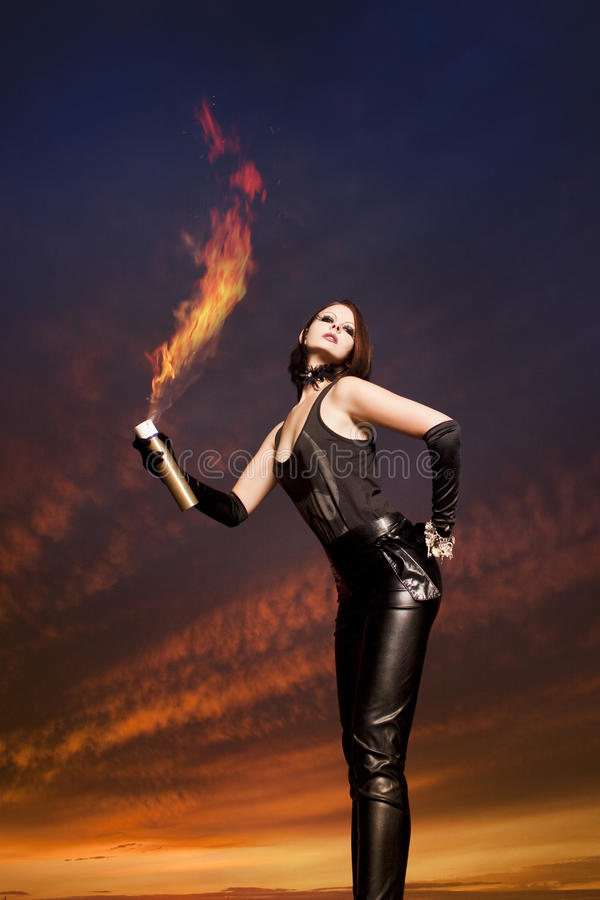 Beautiful young woman dancing. In front of a cloudy sky royalty free stock image