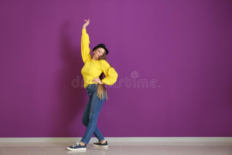 Beautiful young woman dancing near color wall stock images