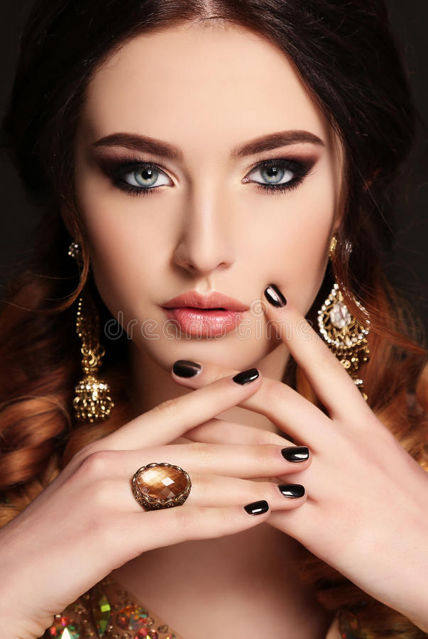 Beautiful young woman with dark hair and bright makeup,with bijou. Fashion studio photo of beautiful young woman with dark hair and bright makeup,with bijou stock photo