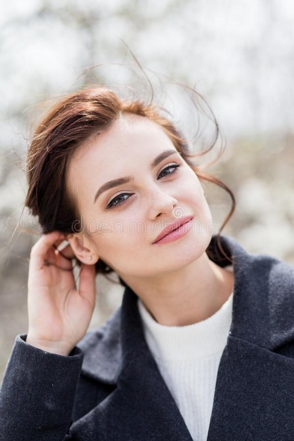 Beautiful young woman with dark hair in wool coat outdoor. Spring time tenderness stock photos