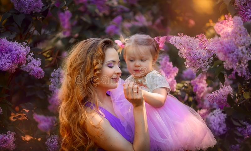 Beautiful young woman with daughter in a blossom park stock images