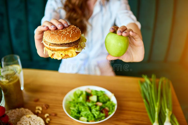 Beautiful young woman decides eating hamburger or apple in kitchen. Cheap junk food vs healthy diet royalty free stock image