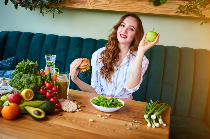 Beautiful young woman decides eating hamburger or apple in kitchen. Cheap junk food vs healthy diet stock images