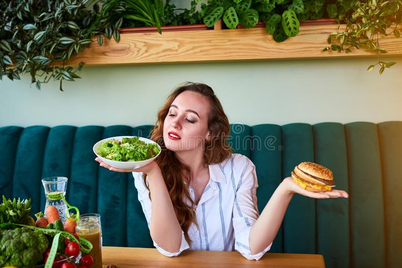 Beautiful young woman decides eating hamburger or fresh salad in kitchen. Cheap junk food vs healthy diet stock image