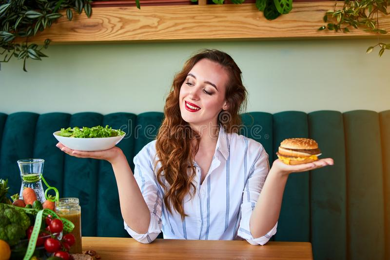 Beautiful young woman decides eating hamburger or fresh salad in kitchen. Cheap junk food vs healthy diet stock images