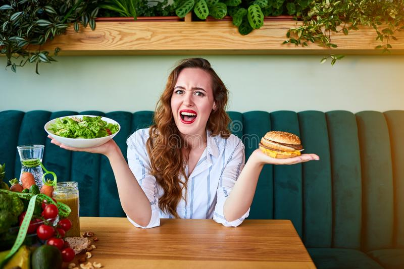 Beautiful young woman decides eating hamburger or fresh salad in kitchen. Cheap junk food vs healthy diet royalty free stock photography
