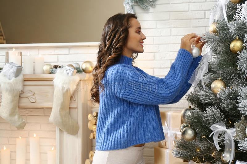 Beautiful young woman decorating Christmas tree stock photography